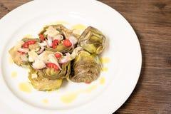 Roman artichokes in a pan. With fresh Tropea onion, Sicilian chilli pepper all garnish with oil and lemon cream Stock Image