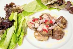 Roman artichokes in a pan. With fresh Tropea onion, Sicilian chilli pepper all garnish with oil and lemon cream Stock Photo