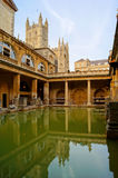 Roman Baths. Ancient Roman Baths at Bath England at dusk. Bath Abbey can be seen behind Royalty Free Stock Image