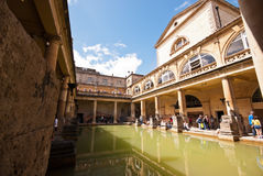 Roman Baths in Bath. Thermal roman pool with cathedral, column ans statues in a sunny day. - u;tra wide lens - Bath (UK) 07/2015 Stock Image