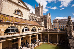 Roman Baths in Bath. Thermal roman pool with cathedral, column ans statues in a sunny day. - u;tra wide lens - Bath (UK) 07/2015 Royalty Free Stock Image