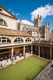 Roman Baths in Bath. Thermal roman pool with cathedral, column ans statues in a sunny day. - u;tra wide lens - Bath (UK) 07/2015 Stock Images
