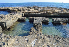 Roman Baths In The Sea. El Campello's Roman Baths cut into the volcanic rock Stock Images