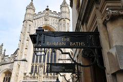 Roman Baths Sign. Old Signs outside the Roman Baths With Bath Abbey in the Background - The Baths are a Popular Tourist Attraction in the Somerset City of Bath Royalty Free Stock Image