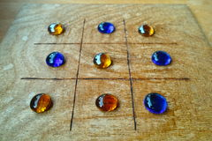 Roman board game Tic-Tac-Toe. An ancient board game with its blue and amber-colored playing stones on a table. A replication which games Romans played royalty free stock images