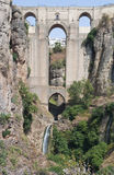 Roman bridge. Of four arches located in the town of Ronda in the Spanish province of Malaga. It is on port amid a rock cliff surrounded by vegetation and a Stock Photography