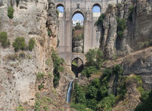 Roman bridge. Of several arches with a waterfall, surrounded by greenery is located in the Spanish town of Ronda in the province of Malaga Royalty Free Stock Photography