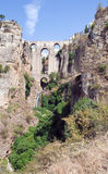 Roman bridge. Of four arches Located in the town of Ronda in the Spanish province of Malaga. It is on a rock cliff amid port Surrounded by vegetation and a Royalty Free Stock Photos