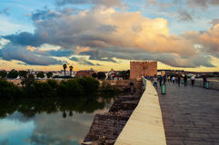 Roman bridge across the Guadalquivir river in Cordoba. Roman bridge across the Guadalquivir river and Calagorra Tower at sunset with people walking on them in royalty free stock image