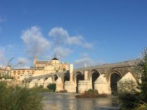 The roman bridge crossing the Guadalquivir river. In Cordoba, Espana. Surrounded by water and what is also a nature reserve on the river, for abundant plant royalty free stock image