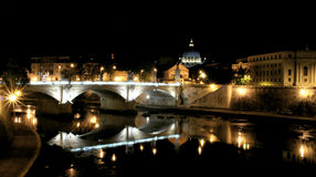 Roman bridge by night. Rome, bridge and river at night, st. Peter's dome in background Royalty Free Stock Images