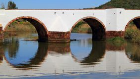 Roman Bridge in Silves, Algarve Portugal. Ancient Roman Bridge reflecting on the Arade River in Historical town of Silves, Faro District, Algarve, Portugal Royalty Free Stock Photos