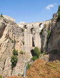Roman bridge Surrounded by vegetation. Roman bridge of four arches Located in the town of Ronda in the Spanish province of Malaga. It is on a rock cliff amid Royalty Free Stock Photo