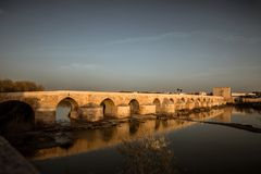 Roman brug bij zonsondergang in Cordoba stock afbeelding