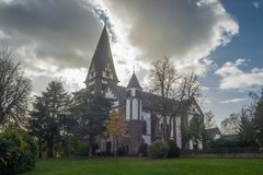 Roman Catholic Church under Clouds. A roman catholic church in central Europe under a cloudy sky with the sun behind it Royalty Free Stock Photography