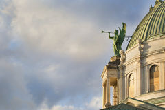 A Roman Catholic Church. A copper-clad angel decorating the dome of a Roman Catholic Church trumpets the ending of a mid-Autumn day Royalty Free Stock Photos