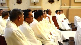 Roman Catholic priests seated chatting listening to homily during congregation mass. San Pablo City, Laguna, Philippines - October 20, 2016:Roman Catholic stock video footage
