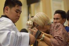 Roman Catholic Women ges sällsynt möjlighet av att kyssa den heliga monstrans under en stadfestlighet royaltyfri fotografi