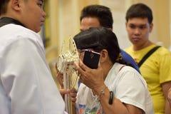 Roman Catholic Women ges sällsynt möjlighet av att kyssa den heliga monstrans under en stadfestlighet royaltyfria bilder