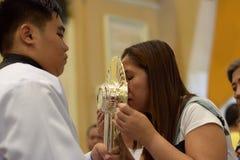 Roman Catholic Women ges sällsynt möjlighet av att kyssa den heliga monstrans under en stadfestlighet arkivfoto