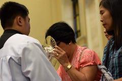 Roman Catholic Women werden seltene Möglichkeit der küssenden heiligen Monstranz während einer Stadtfestlichkeit gegeben lizenzfreie stockfotografie