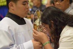 Roman Catholic Women wordt gegeven zeldzame kans om Heilige Monstrans tijdens een stadsfestiviteit te kussen stock afbeeldingen