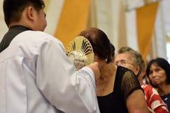 Roman Catholic Women wordt gegeven zeldzame kans om Heilige Monstrans tijdens een stadsfestiviteit te kussen royalty-vrije stock afbeelding