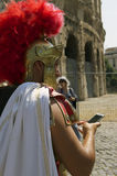 Roman Centurion med mobiltelefonen på Colosseumen i Rome Royaltyfri Foto