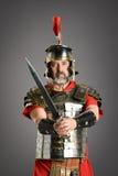 Roman Centurion With Sword. Portrait of Roman centurion holding sword over a neutral background Stock Photo