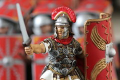 Roman centurion toy figure. Close-up of a roman soldier figure, with the gesture of attacking - his cohort formation in the background blurred Royalty Free Stock Photos