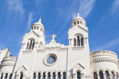 Roman church. Beautiful white building of church against blue sky and cloudscape Stock Image