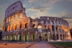 Roman Coliseum enlighted i aftonen under molnen arkivbild