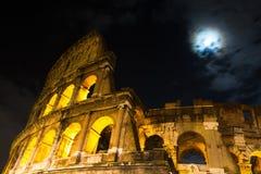 Roman Coliseum sotto una luna piena fotografia stock