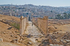 Roman colonnade and modern Jerash, Jordan. Well preserved and restored ruins of Jerash (Gerasa, Greco-Roman city of Antiquity), Jordan with modern city in Royalty Free Stock Photo