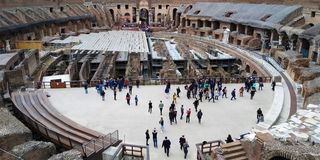 Roman Colosseum interior, Roma, Italy with Tourist. Interior of the Colosseum in Rome, Italy. its construction started in 72 AD under the emperor Vespasian and stock images