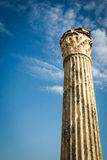 Roman column. Low angle view of an ancient Roman column offset against a bright blue sky with copy space Royalty Free Stock Photo