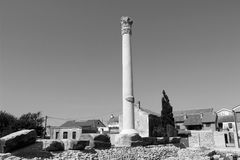 Roman column with mediterranian houses and stone brickwork black and white Royalty Free Stock Images
