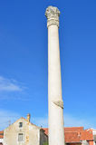Roman Column. A reconstructed tall roman column with a corinthian capital from a ruined temple in the middle of a town Stock Photo