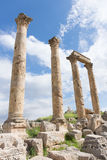 Roman Columns Jerash. Ancient Roman columns with ornately carved capitals and a stone beam amidst a pile of rubble in Jerash, Jordan. Blue sky with clouds is Stock Photo
