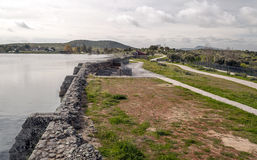 Roman dam. Located in the swamp of Proserpina in the Spanish city of Merida, is aside the swamp water, across the bottom a few trees and some houses Royalty Free Stock Photos