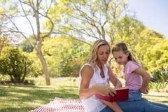 Roman de lecture de mère et de fille en parc Photographie stock libre de droits