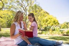 Roman de lecture de mère et de fille en parc Image stock