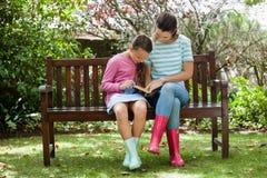 Roman de lecture de mère et de fille tout en se reposant sur le banc en bois Images libres de droits