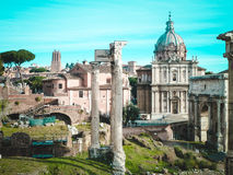 Roman Forum, in the center - columns of Temple  Saturn,Santi Luca e Martino. Roman Forum  - square in the heart of ancient Rome, along with surrounding buildings Royalty Free Stock Images