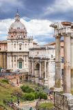Roman Forum, Rome`s historic center, Italy. View of Roman Forum with ancient ruins of temple, columns of Saturn, Triumphal Arch of Septimius Severus, Rome, Italy Stock Photos