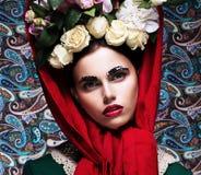 Roman. Förädlad ung kvinna med gruppen av färgrika blommor. Skönhet Arkivfoto