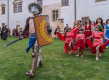 Roman gladiator in battle costume and a group of young Roman gir Royalty Free Stock Photography