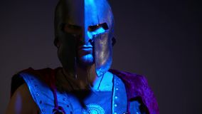 The Roman gladiator in a heavy helmet, leather armor and red raincoat looks into the camera standing in the ultraviolet stock video