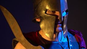 The Roman gladiator in a helmet, leather armor and red raincoat holds a rusty sword on his shoulder and looks away. The Roman gladiator in a helmet and armor stock footage