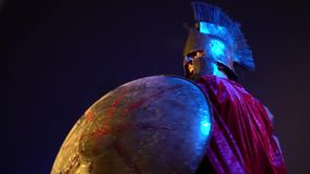 Roman gladiator in leather armor, helmet and red raincoat is covered with a round shield and strikes with a sword, slow